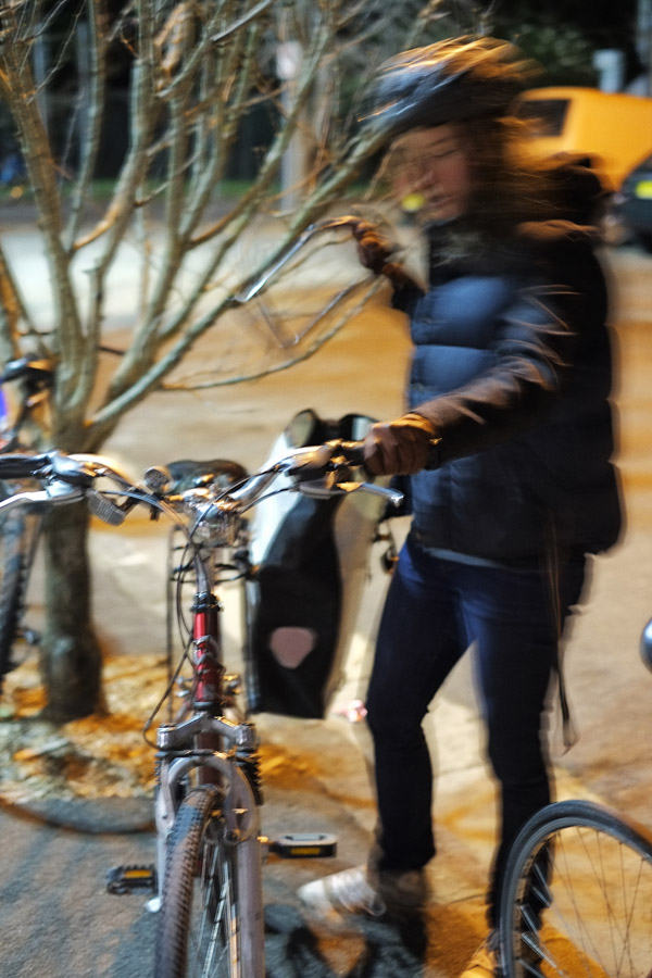 Locking the bike, Black puffer vest, blue jeans and runners, Sydney Street Style.