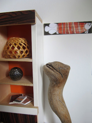Close up of a modern dolls' house miniature scene of a 1970s display cabinet holding a selection of art objects and books. Next to it is a wooden sculpture, and an aboriginal artwork on the wall.