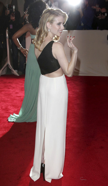 Emma Roberts waving to the photographers in a white one-shoulder Michael Kors silk crepe column gown with black Paillette detail and a midriff-revealing cut-out and a pair of Chopard's diamond earrings at the 2011  MET Gala.