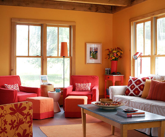 the bold orange accent color looks shocking against the icy blue walls but this unexpected color scheme creates a fun twist on the otherwise placid room - Living Room Colour Schemes 2011
