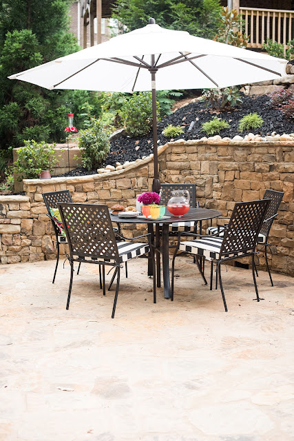 stone patio table and chairs, black and white outdoor, plants, backyard, landscaping