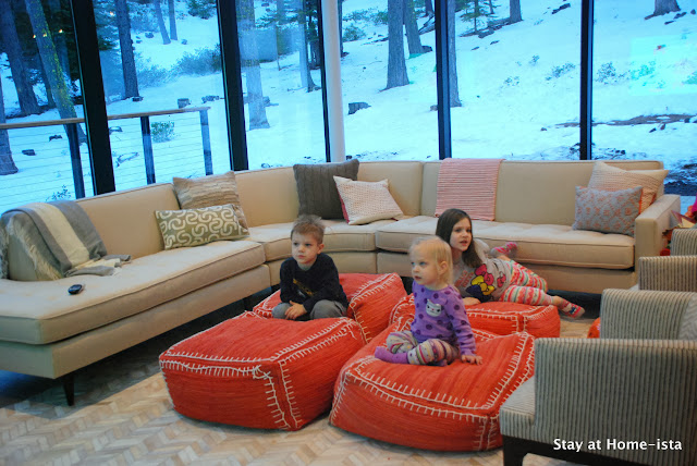 Kids watching TV on poufs in the living room