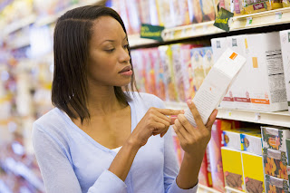 woman reading food packaging closely, which is the only way to determine what is really in your food