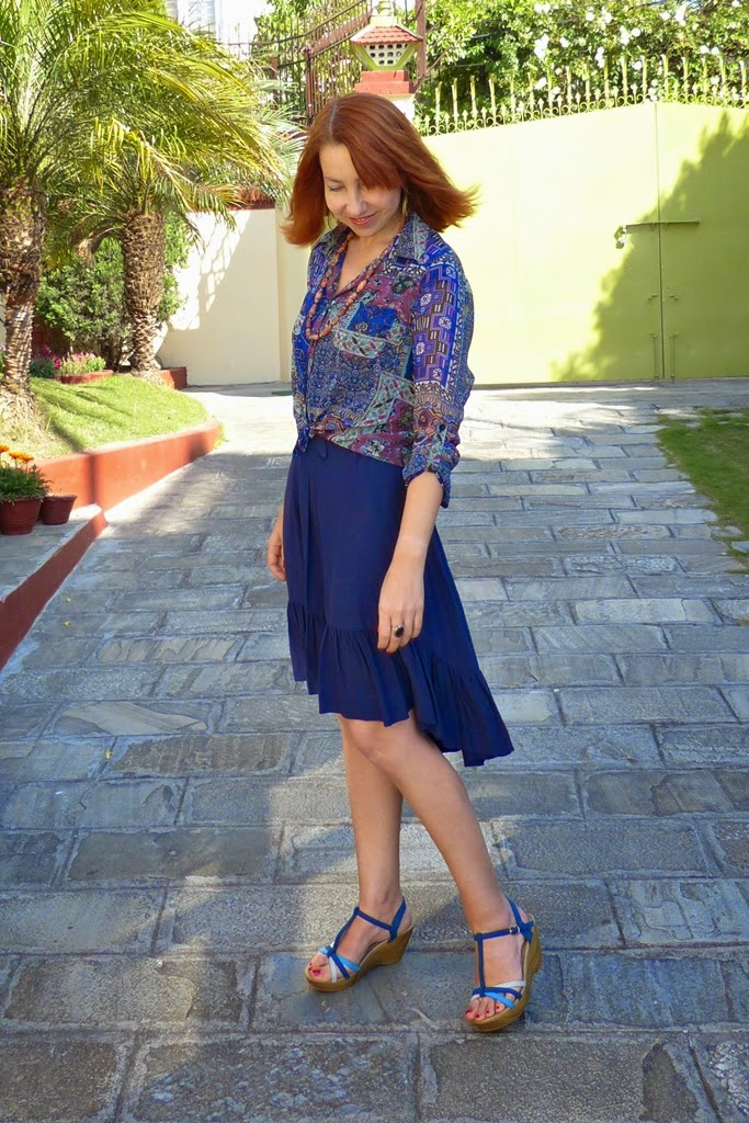Navy blue dress with asymmetrical hem worn with printed blouse