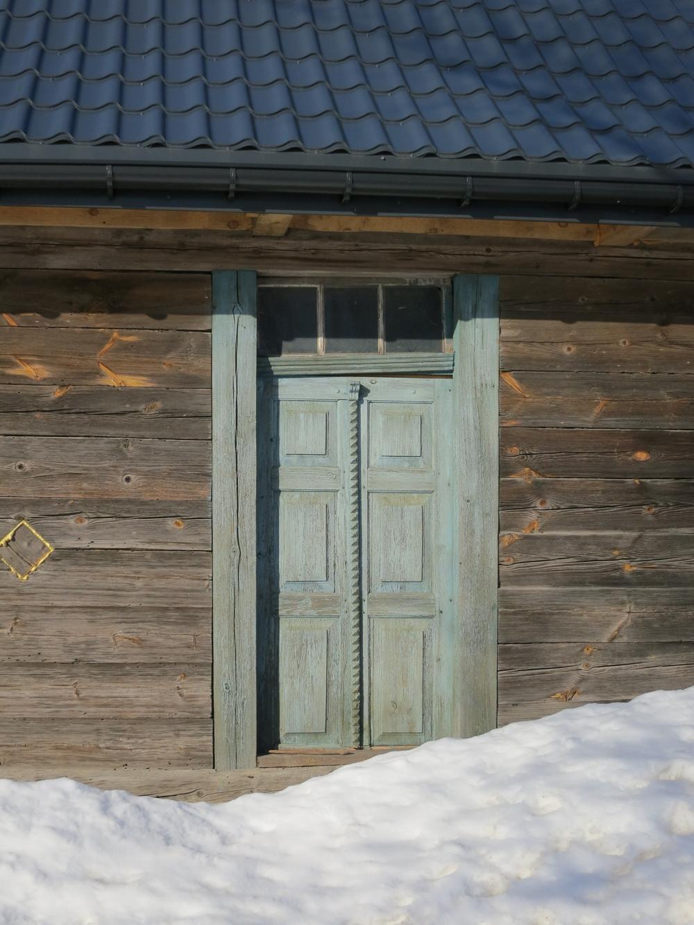 Detal drzwi w chacie w Harkawiczach, drzwi są seledynowe, przed drzwiami wielka czapa śniegu