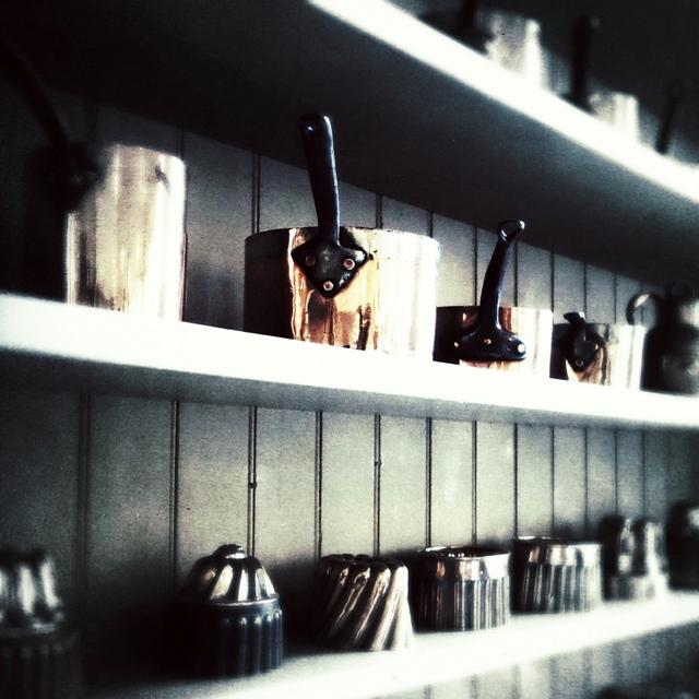 Old copper saucepans and jellies moulds on kitchen shelves, Penhryn Castle.