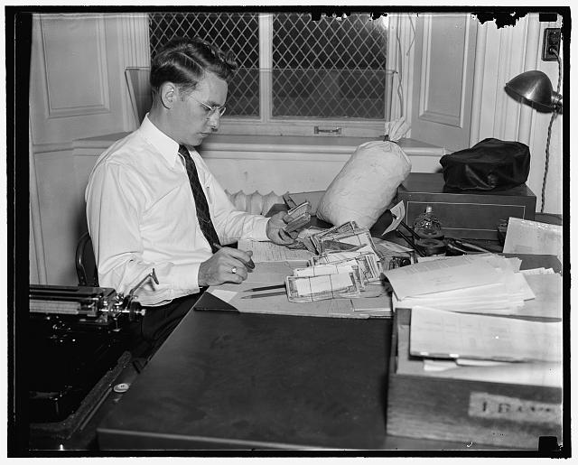 Checking over confiscated counterfeit currency at the Secret Service Div. of the Treasury, 10/38
