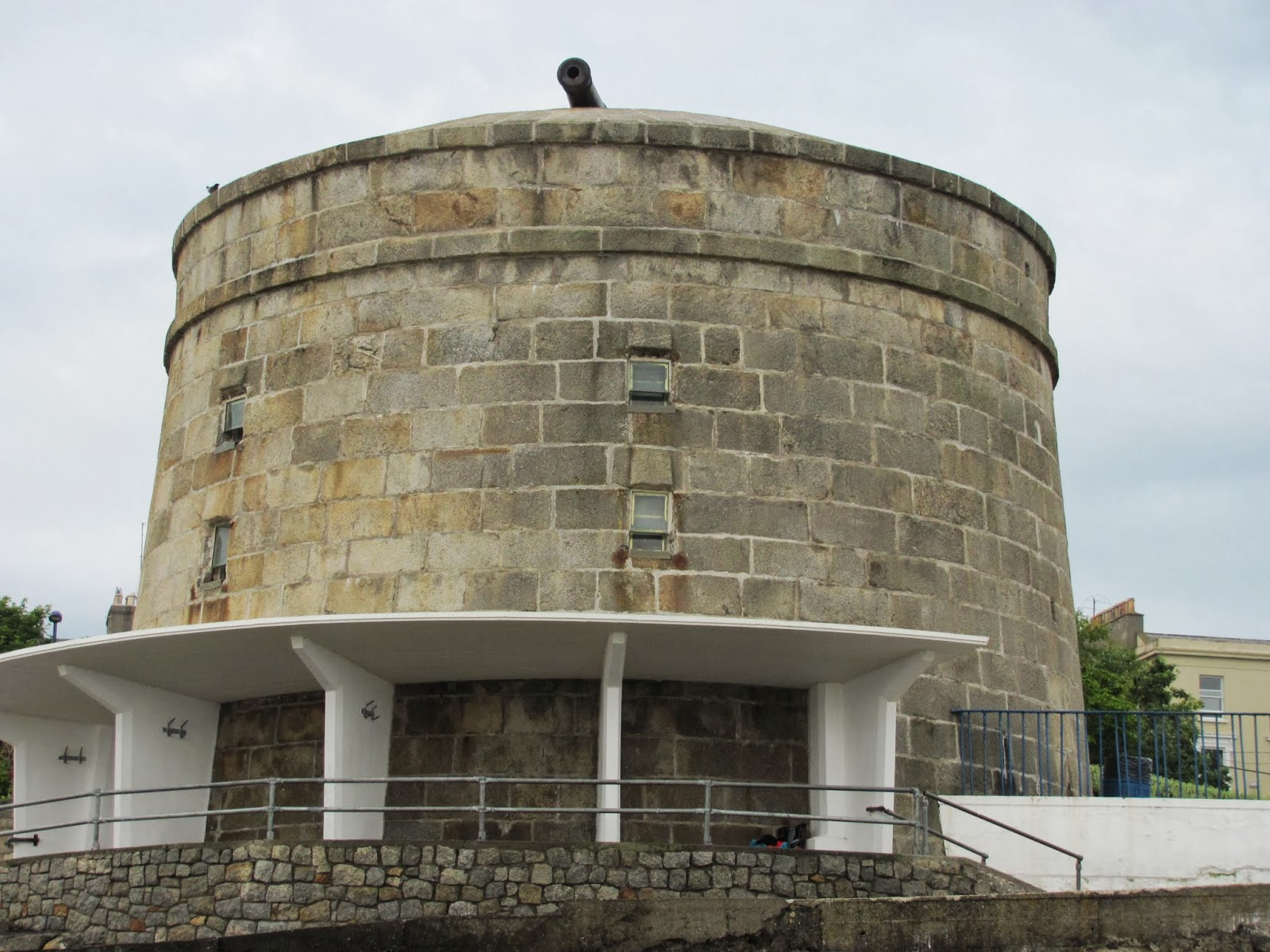 A cylindrical tower with a cannon on top protects the bay from historical marauders at Seapoint Beach, Dublin, Ireland