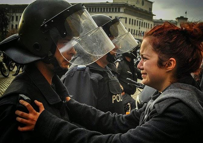 Полицейский и демонстрантка плачут вместе во время акции протеста в Софии, Болгария, 2013 год. Студенты и другие протестующие вышли на улицы города в знак протеста против бедности и коррупции. В итоге многие пострадали.