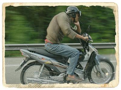 mamat menunggang motor sambil termenung