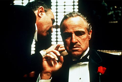 Whispering in Marlon Brando's ear in his role as The Godfather movieloversreviews.blogspot.com