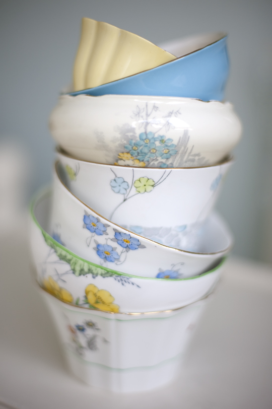 a stack of blue and yellow floral vintage sugar bowls