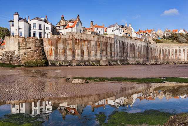 Reflection of the pretty village of Robins Hood's Bay in North Yorkshire by Martyn Ferry Photography