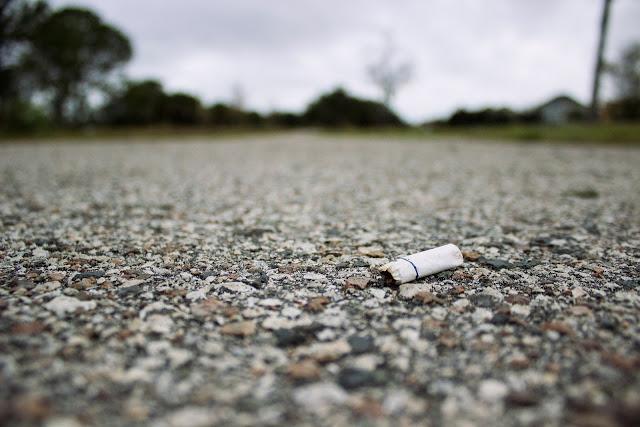 Un mégot de cigarette par terre.