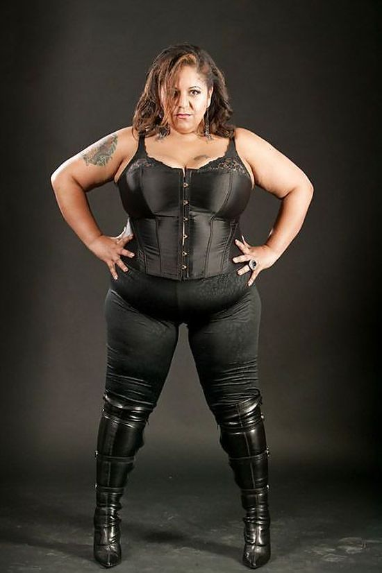 strong dominant woman with curves, dressed in black boots and bustier with her hands in her side.