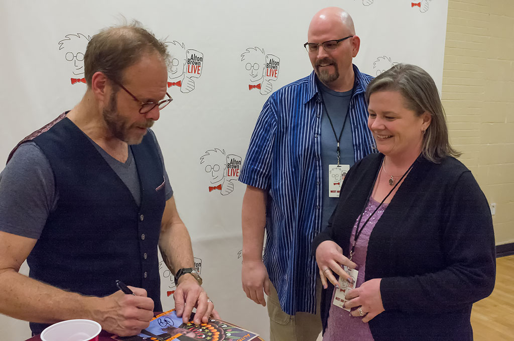 Alton Brown signs a photo