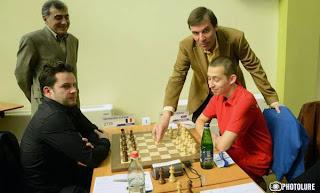 Ci-contre, le président bulgare de l'European Chess Union (ECU) Silvio Danailov joue le premier coup symbolique de la partie de la table 1 entre Petenyi et Bacrot, en présence du grand-maître arménien Smbat Lputian © site officiel