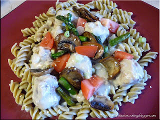 asparagus fusilli with pork balls in mushroom sauce topped with sauteed mushrooms and asparagus and chopped fresh green onions and tomatoes