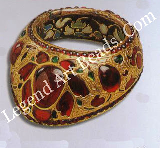THUMB RING Mughal; c.1625 H: 3 7 CM Dam: 3 CM Courtesy Victoria and Albert Museum, London (IM 207-1920) Set with rubies and emeralds individually cut to design requirement, the inside of the ring is enamelled in opaque white blue pale green and black, illustrating European design influence a break from the traditional Mughal palette of vibrant greens reds and blues.