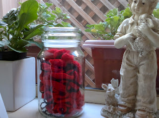 Windowsill looking out to a trellis (left to right) green plant in white pot, glass jar containing crochetd poppies, terracotta-coloured windowbox with geranium foliage, statue of boy with bunnies.