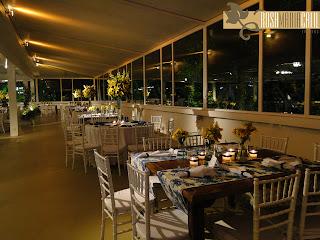 mesa quadrada de madeira teca, arranjos altos e baixos com flores amarelas, laço Chanel