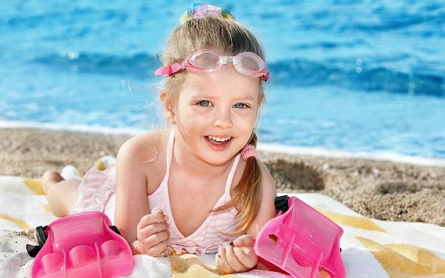Meisje met zwemspullen op het strand