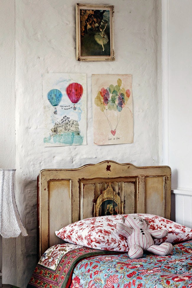 Sypialnia w stylu surtykalnym, stara i drewniana rama lóżka, nierówne białe ściany, ilustracje kolorowe na ścieni, kolorowa pościel w kwiaty