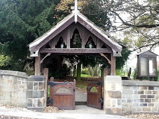A wooden lychgate over a double wooden gate set in a stone wall.  Behind are trees in a graveyard.