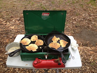 two cast iron pans on a Coleman camp stove cooking chocolate chip panckes while camping.