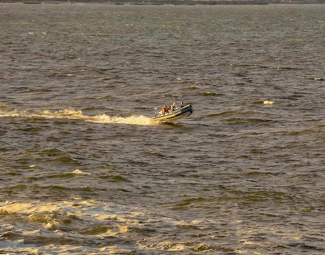 Lancha con cuatro tripulantes surcando el mar a alta velocidad sobre las olas