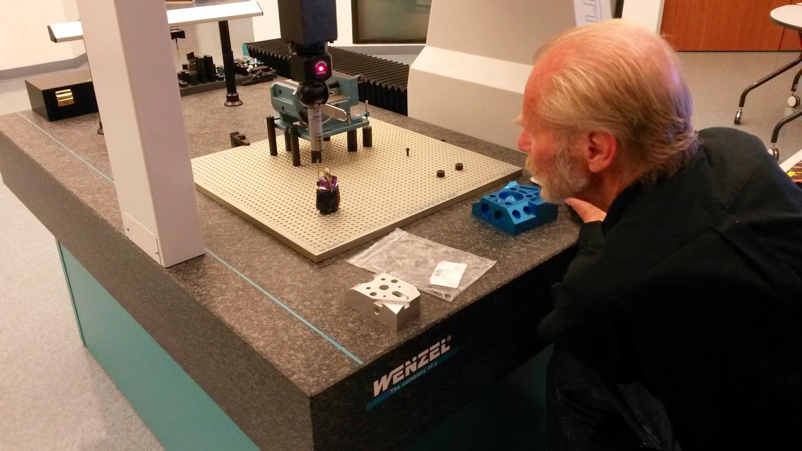 Man using CMM machine to inspect perfume bottle
