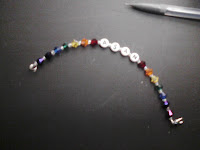 Bracelet that says ASAN, has crystals in rainbow order to each side