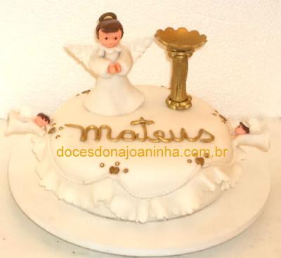 Bolo decorado com pia batismal dourada, anjo e anjinhos voando na lateral, borda de babadinhos o nome do bebê dourado