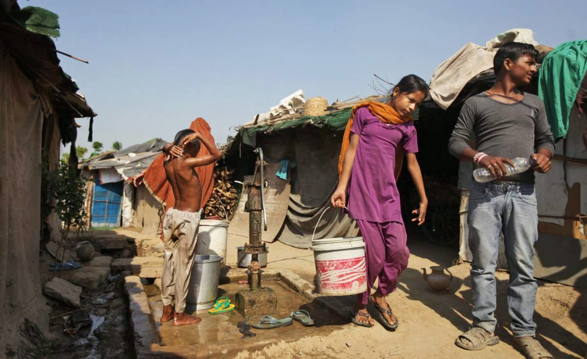 A young girl fetches water from a hand pump in an impoverished settlement in New Delhi, March 21, 2015. (Credit: Altaf Qadri—AP) Click to Enlarge.