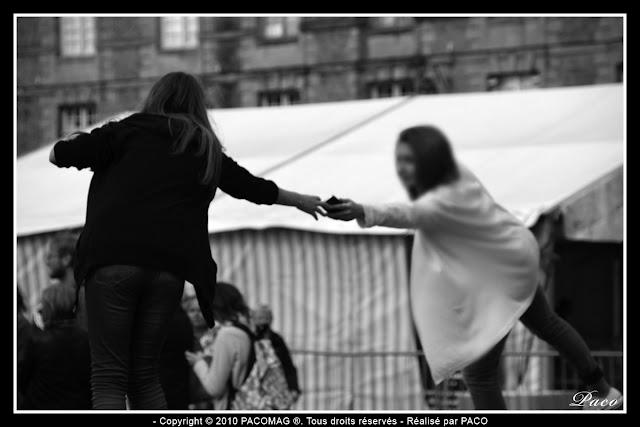 deux jeunes filles en équilibre sur un plot de la place ducale se passent un portable lors du festival des marionnettes