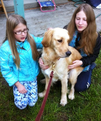 Sarah and her sister pose with Ella (Golden Retriever) in their yard on the grass.