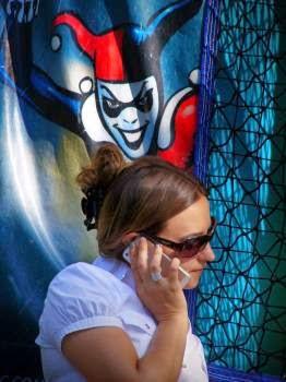 Una donna al cellulare è spiata alle spalle da un giullare malvagio dipinto su un muro