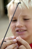 A boy putting bait on a fish hook.