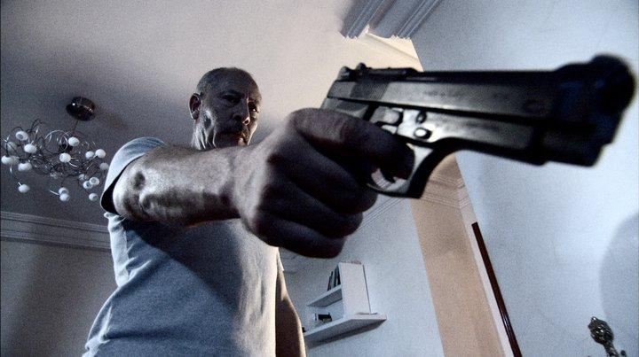 fotograma con Hakim Noury empuñando una pistola, plano contrapicado. imagen con tonos fríos