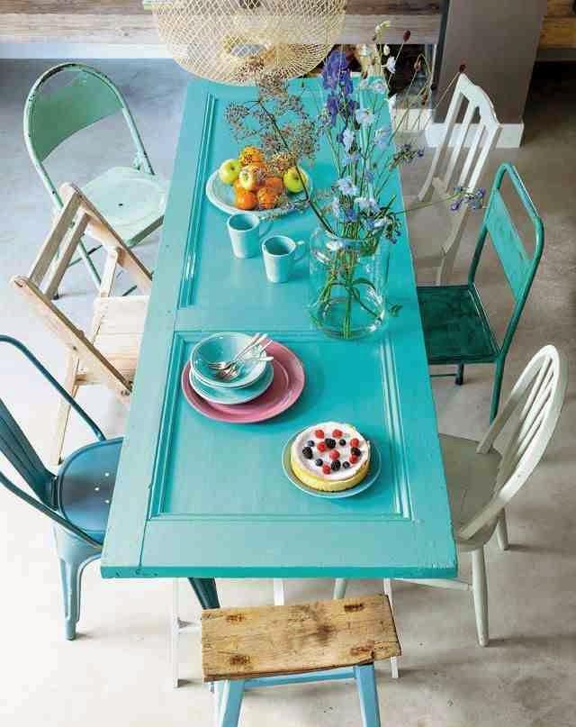 Turkusowe drzwi jako blat stołu, niebieskie krzesło tolix, metalowe kzresła, nebieski taboret z drewniany siedziskiem, gałęzie w wazonie