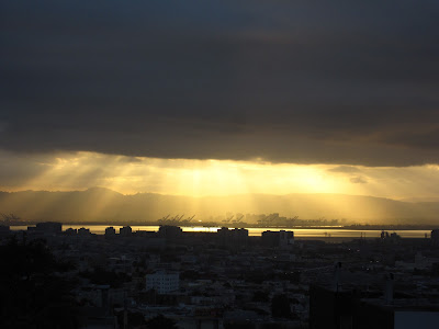 the sun breaks through clouds over the San Francisco Bay looking east from San Francisco
