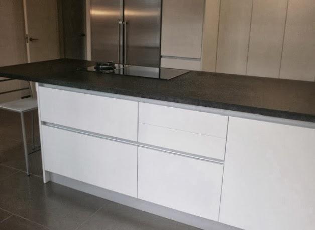 al fondo la zona de fregadero con pared frontal del mismo granito negro integrado y a su lado columna de horno y microondas