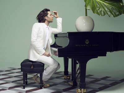 Rufus Wainwright in white suit seated at Steinway piano