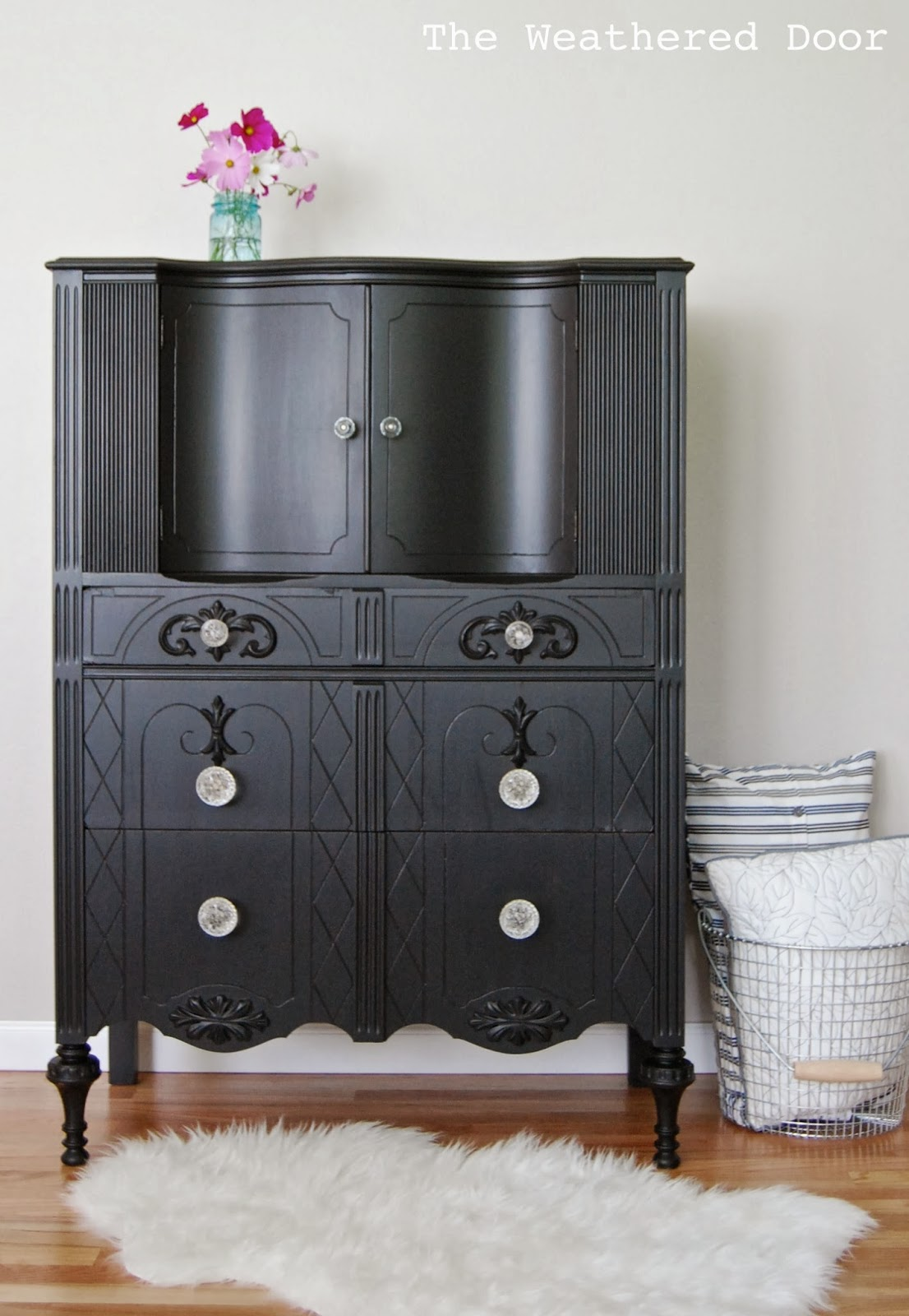 A Tall Black Dresser With Glass Knobs The Weathered Door