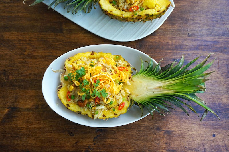 thai style pineapple fried rice served in a hollowed out pineapple ...