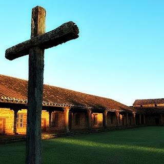 Redução de San Cosme y Damián ao anoitecer. Cruz em primeiro plano e igreja no fundo, à esquerda.