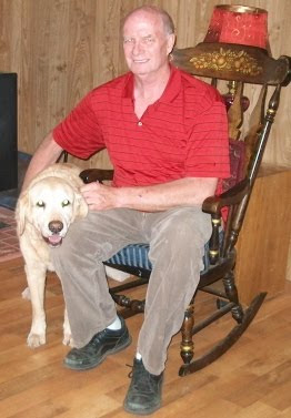 Larry in rocking chair with his arm around yellow Lab Galleon