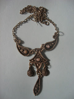 Unusual and striking necklace. Metal is highly textured. Appears to be a dark bronze with a long chain. Two tear-drops or paisley-shaped pieces with round bumpy details curve inward and connect with a four-pointed star with a round ornament in the middle and smaller ones in each point, also with a bumpy ridge all around. Hanging from that are spiral dangles off of the two side points and a long teardrop also with raised bumps going down the inside.