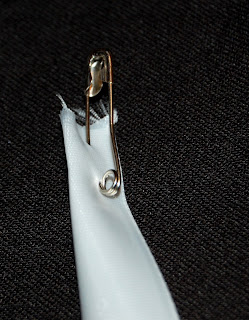 use safetly pin to guide ribbon through casing