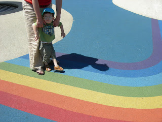 un niño camina con ayuda de un adulto sobre un pavimento de colores